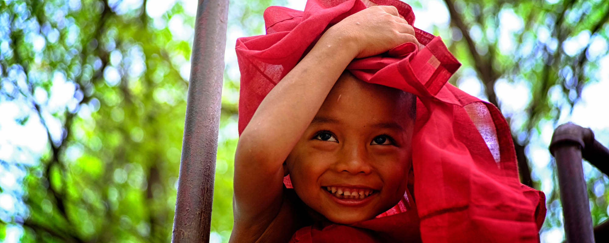 boy holding textile over his head